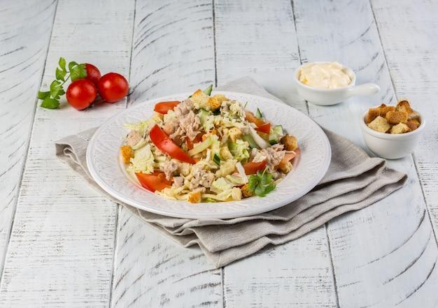 Klassischer caesar-salat mit gebratenem huhn, eiern, salat, speck, parmesan und tomaten