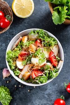 Klassischer caesar-salat mit hähnchenfilet und parmesankäse. chicken caesar salad. ansicht von oben, kopienraum.