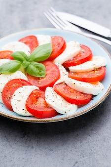 Klassischer caprese-salat. mozzarella-tomaten und basilikum.