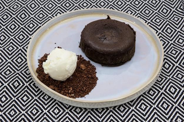 Klassischer fondant mit flüssiger schokoladenmitte. serviert mit hausgemachtem eis und schokoladenboden. nahansicht.