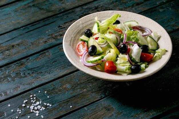 Klassischer gemüsesalat mit tomaten, gurken, zwiebeln, blattsalaten und schwarzen oliven in weißer keramikplatte. dunkler holztisch.