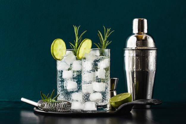 Klassischer gin tonic cocktail mit rosmarinzweigen in hohen gläsern auf einem tisch mit barzubehör