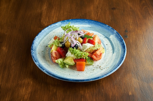 Klassischer griechischer salat mit tomaten, gurken, roten zwiebeln, feta-käse und oliven, serviert in einem blauen teller auf einer holzoberfläche