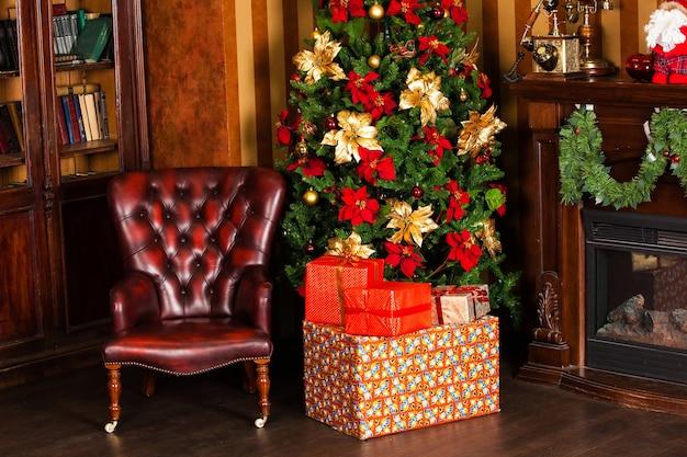Klassischer grüner baum verziert mit geschenken unter baum