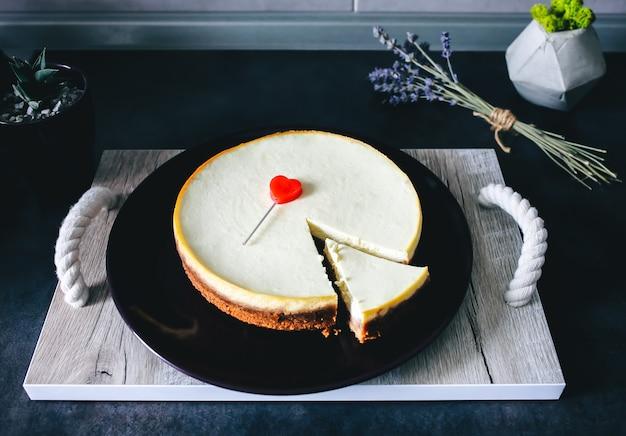 Klassischer hausgemachter new yorker käsekuchen liegt auf einem dunkelvioletten teller auf einem holztablett mit seilgriffen auf einem grauen küchentisch. lavendel und saftig im hintergrund. rotes herz zum valentinstag geschenk
