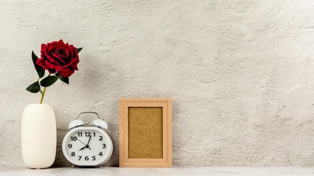 Klassischer hölzerner fotorahmen mit wecker und einer roten rose. - leerzeichen für nachrichten- und werbehintergrund.