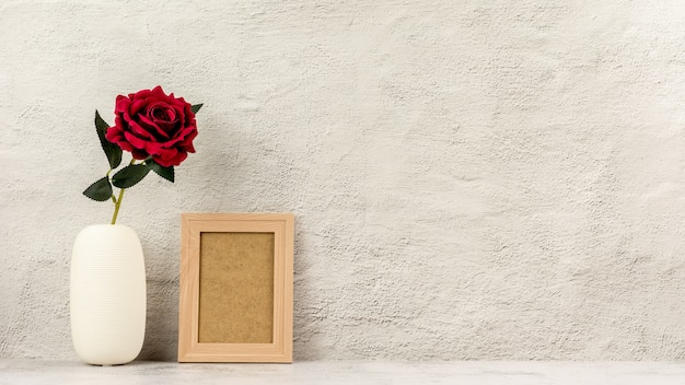 Klassischer hölzerner fotorahmen und eine rote rose im vase