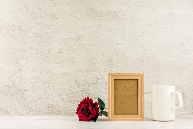 Klassischer hölzerner fotorahmen und rotrose mit einer weißen kaffeetasse.