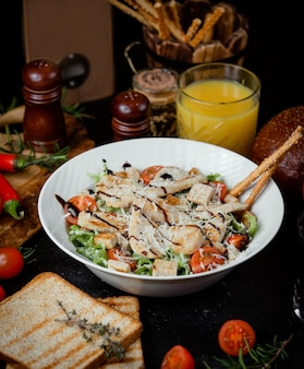 Klassischer hühnchen-caesar-salat mit geriebenem parmesan und crackern