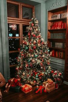 Klassischer innenraum des dunklen wohnzimmers und des neuen jahres der bibliothek mit verziertem weihnachtsbaum