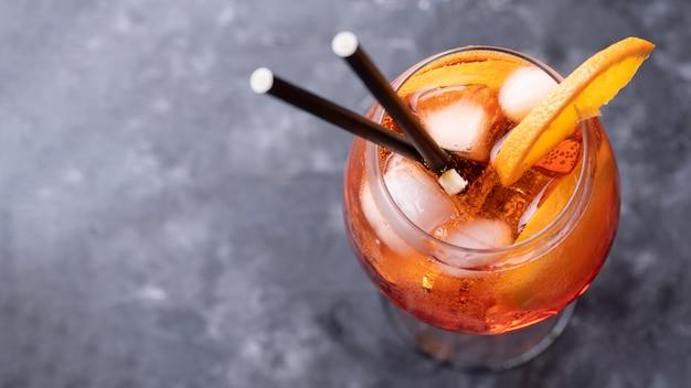Klassischer italienischer aperitif-aperol-spritz-cocktail im glas mit orangenscheibe auf dunkler wand, draufsicht