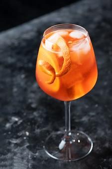 Klassischer italienischer aperol-spritz-cocktail im glas auf einer dunklen nahaufnahme