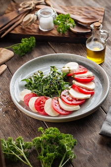 Klassischer italienischer caprese-salat auf dem holztisch