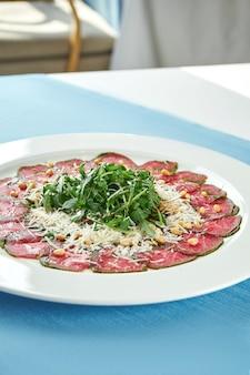 Klassischer italienischer salat - rindfleisch vitello tonato mit rucola, parmesan und trüffelsauce in einem weißen teller auf blauer tischdecke. nahaufnahme, selektiver fokus