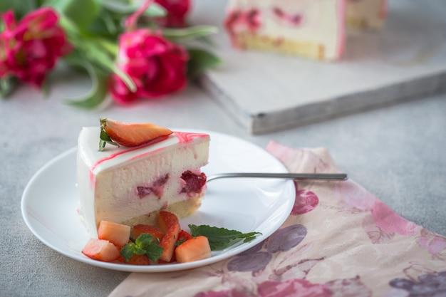 Klassischer käsekuchen new york in scheiben geschnittenes stück käsekuchen mit frischen erdbeeren und tulpen
