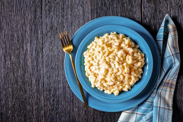 Klassischer mac und käse in einer blauen schüssel mit goldener gabel und serviette auf einem holztisch, horizontale ansicht von oben, flache lage, freier raum