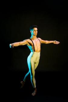 Klassischer männlicher balletttänzer, der im scheinwerfer durchführt