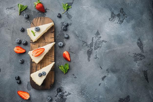 Klassischer new yorker käsekuchen, in scheiben geschnitten, auf grauem tisch, flache lage mit draufsicht