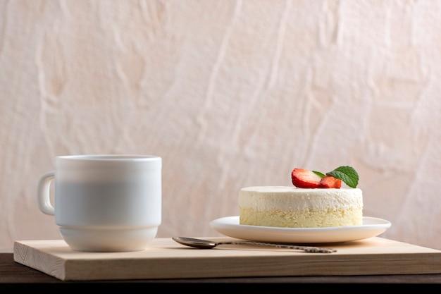 Klassischer new yorker käsekuchen und eine tasse kaffee oder tee. dessert im café.