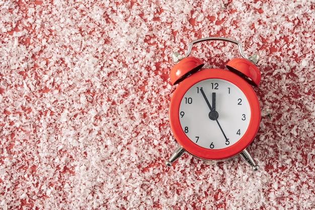 Klassischer retro-wecker auf rotem hintergrund mit weißem schnee und kopienraum für texteinladungen oder -karten. minimales trendkonzept für weihnachten und neujahr.