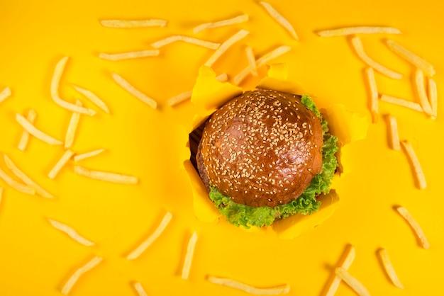 Klassischer rindfleischburger, umgeben von pommes frites