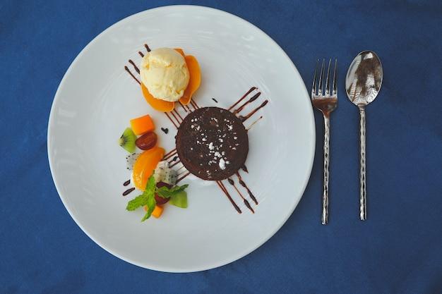 Klassischer schokoladen-brownie serviert mit früchten und vanilleeis