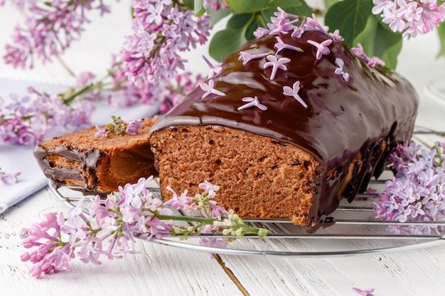 Klassischer schokoladenkuchen auf einem weißen tisch mit blumen