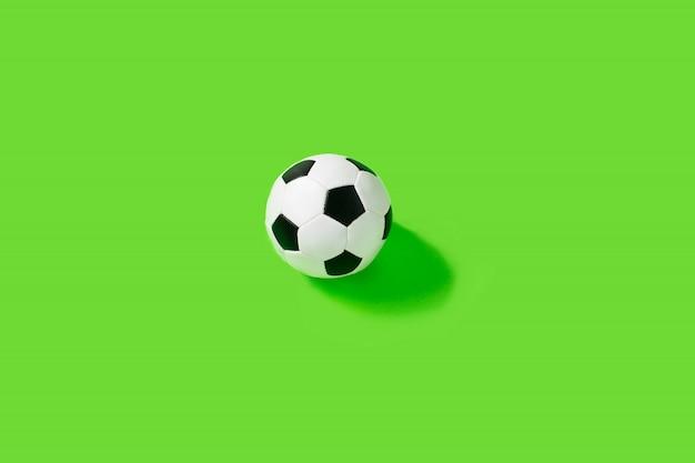 Klassischer schwarzweiss-fußball auf grüner wand.