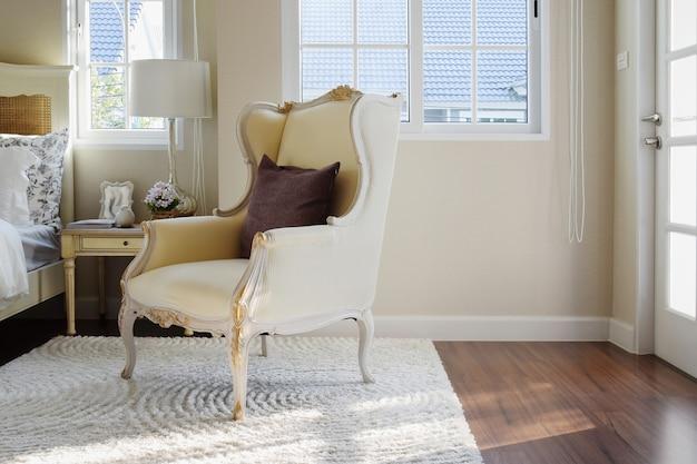 Klassischer stuhl mit braunem kissen auf teppich im weinleseart-schlafzimmerinnenraum