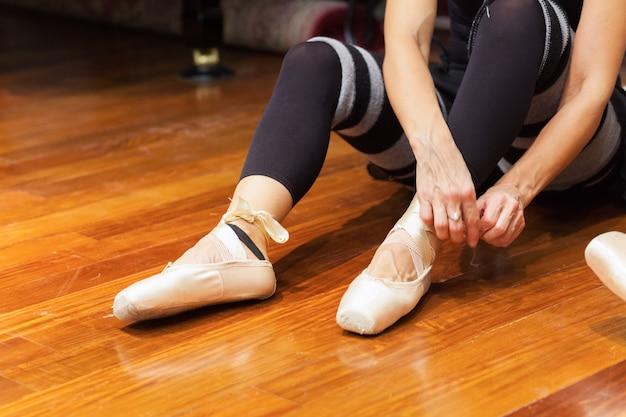 Klassischer tänzer, der ihre schuhe justiert