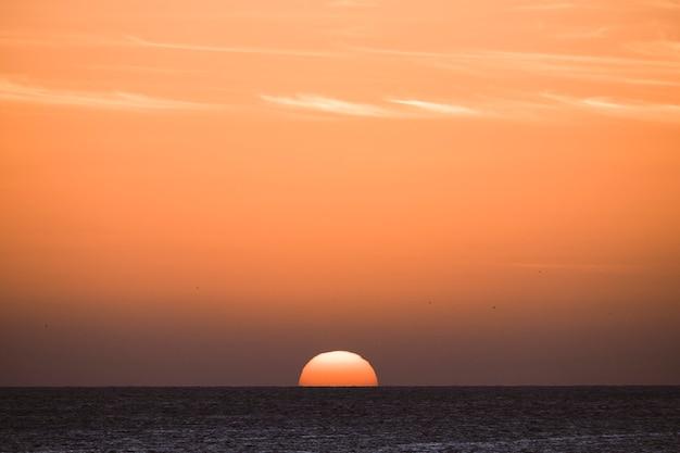 Klassischer tropischer sonnenuntergang oder sonnenaufgang am meereshorizont mit sonne und wasser, die zusammen berühren