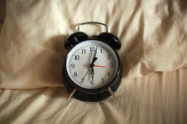 Klassischer wecker, der sechs uhr morgens auf dem bett zeigt