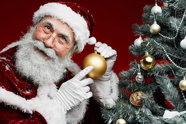 Klassischer weihnachtsmann durch weihnachtsbaum