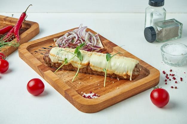 Klassisches arabisches rindfleisch lula kebab mit geschmolzenem käse und zwiebelgarnitur auf holzbrett. appetitliches fleisch auf dem grill.