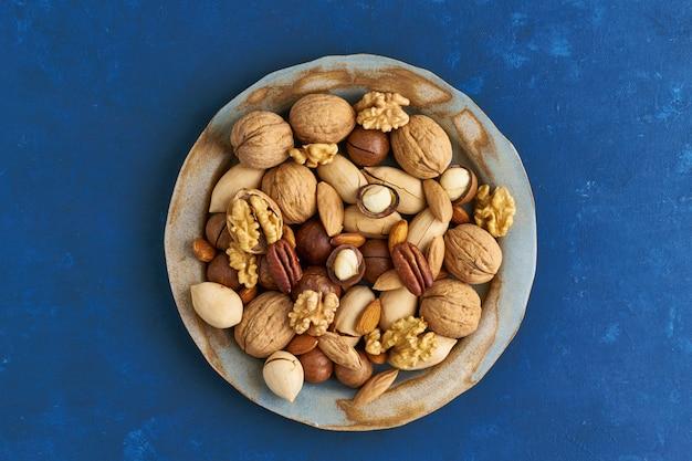 Klassisches blau in lebensmitteln. mischung von nüssen auf platte - walnuss, mandeln, pekannüsse, macadamia