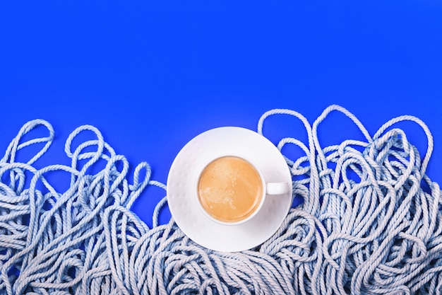 Klassisches blaues layout mit minimalistischem, baumwollweißem seil und tasse kaffee.