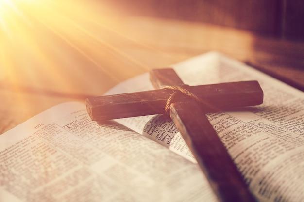 Klassisches christliches holzkreuz auf dem offenen buch