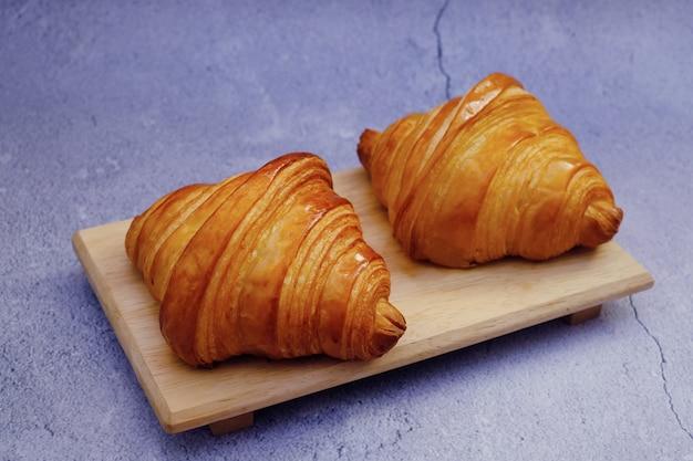Klassisches croissant der nahaufnahmebutter auf holzteller