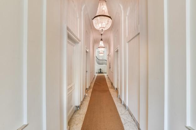 Klassisches design des flurs mit teppich und weißer tür unter kristallleuchtern und mit wendeltreppe am ende