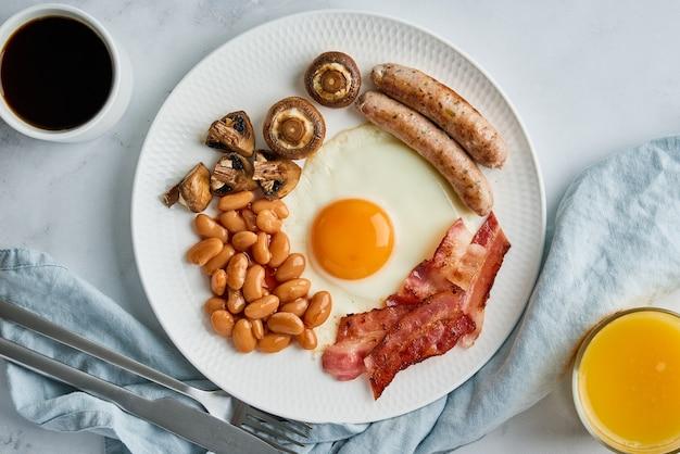 Klassisches englisches frühstück mit eiern würstchen becon bohnen pilze kaffee und orangensaft