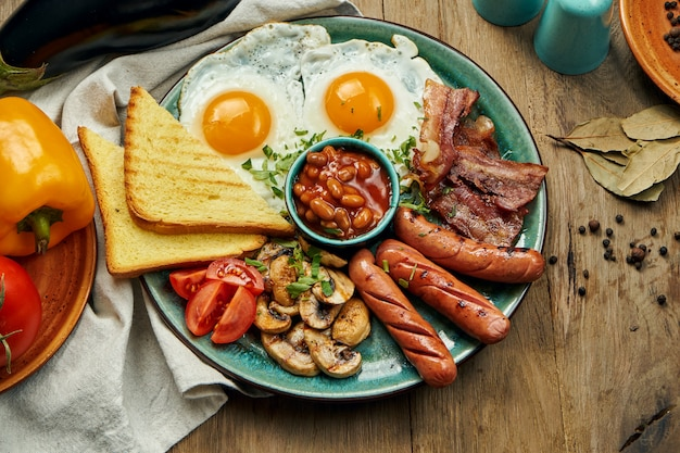 Klassisches englisches frühstück: toast, geräucherte würstchen, speck, spiegeleier, bohnen und gebratene toasts auf einem blauen teller. draufsicht, horizontal. holzoberfläche