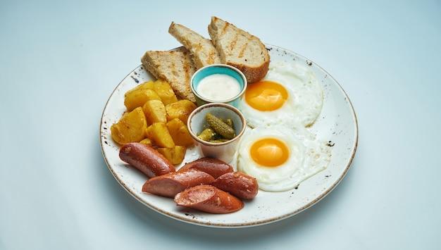 Klassisches englisches frühstück: toast, geräucherte würstchen, spiegeleier, kartoffeln und gebratene toasts auf einem blauen teller auf grauer oberfläche