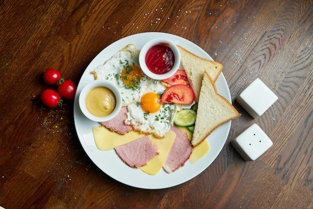 Klassisches englisches frühstück: toast, geräucherte würstchen, spiegeleier, kartoffeln und gebratene toasts auf einem weißen teller