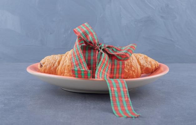 Klassisches französisches frisches croissant auf platte über grauem hintergrund.