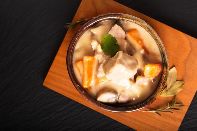 Klassisches französisches lebensmittelkonzept blanquette de veau oder kalbfleisch in der weißwein-soße in der handgemachten keramischen schale mit kopienraum