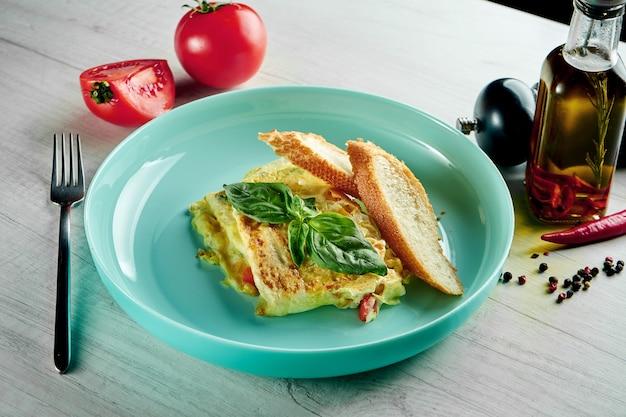 Klassisches französisches omelett mit gemüse und baguette, serviert in einem blauen teller auf einem holztisch. restaurant essen. rührei