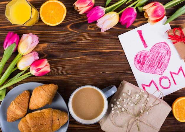 Klassisches frühstück mit tulpen und muttertagspostkarte