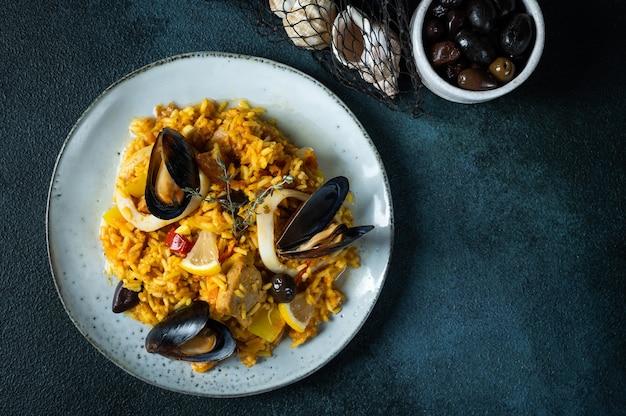Klassisches gericht aus spanien, paella mit meeresfrüchten in der platte auf draufsicht des blauen hintergrundes. spanische paella mit garnelen, klammern, muscheln und frischer zitrone. spanisches essen. komfort essen. reis mit meeresfrüchten.