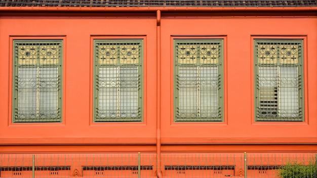 Klassisches grünes hölzernes fenster am orange konkreten gebäude