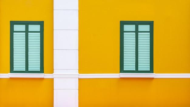 Klassisches grünes und purpleheartfenster am gelben konkreten gebäude.